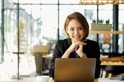Portrait of a young businesswoman sitting with her laptop in the cafe.