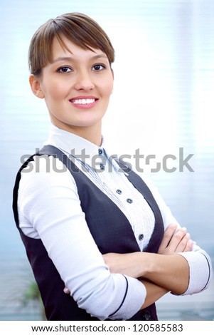 portrait of a young businesswoman smiling against the office background