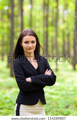 Portrait of a young businesswoman standing with crossed arms in the woods