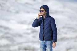 Portrait of a young Caucasian man with phone in hands, wearing warm down jacket with fur hood. Cold winter day, communication at any weather, snow, frost. Looking into distance. Place for your text.