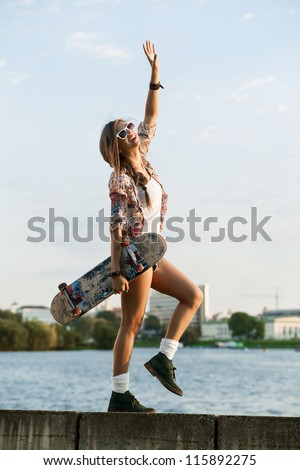 Portrait of a young caucasian skater woman during the sunset, outdoor