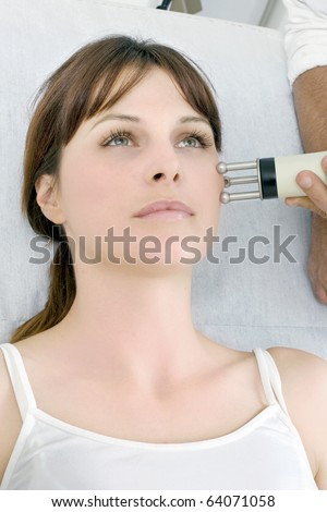 portrait of a young caucasian woman receiving electrostimulation lifting