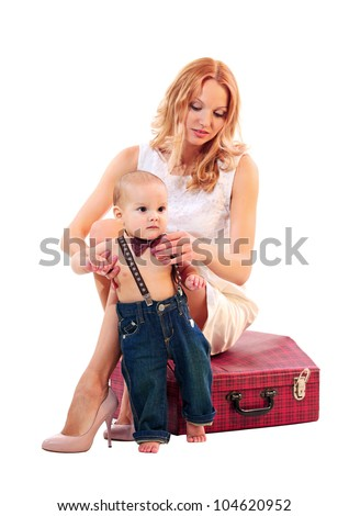 Portrait of a young caucasian woman sitting on a suitcase and her son over white background