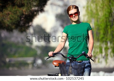 Portrait of a young Caucasian woman with her bike outdoors