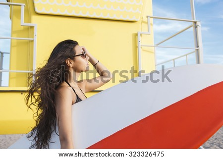 Stock Photo Portrait of a young charming surfer female enjoying sun and free time after her surfing in a beautiful summer day, attractive Latin women hold copy space area surfing board while standing on the beach