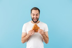 Portrait of a young cheerful excited bearded man wearing t-shirt standing isolated over blue background, showing a sandwich