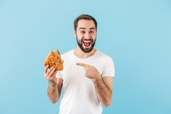 Portrait of a young cheerful excited bearded man wearing t-shirt standing isolated over blue background, pointing finger at sandwich