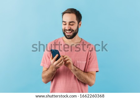 Portrait of a young cheerful excited bearded man wearing t-shirt standing isolated over blue background, using mobile phone