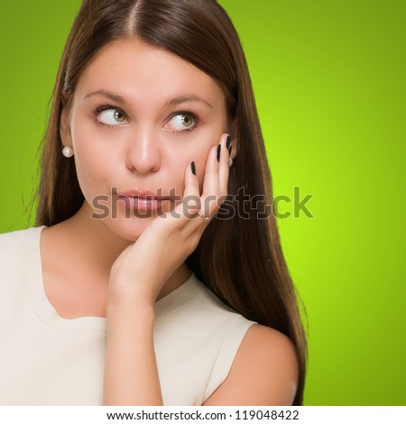 Portrait Of A Young Confused Woman against a green background