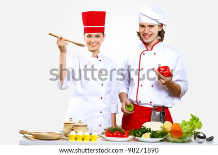 Portrait of a young cook in uniform preparing meal