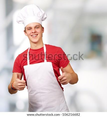portrait of a young cook man doing a success symbol indoor
