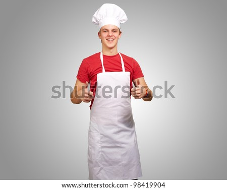 portrait of a young cook man doing a success symbol over a grey background