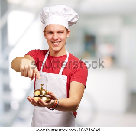 portrait of a young cook man pressing a golden bell indoor