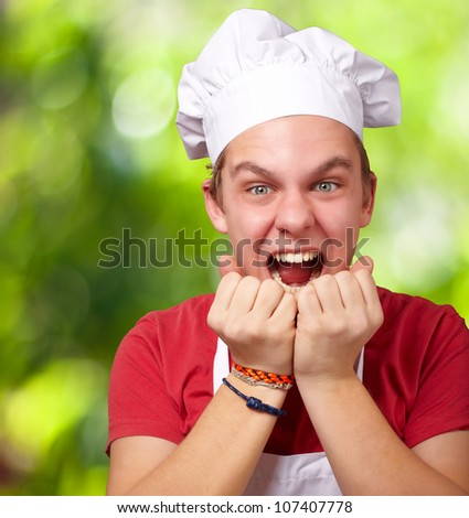portrait of a young cook man screaming against a nature background