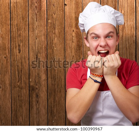 portrait of a young cook man screaming against a wooden wall
