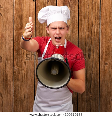 portrait of a young cook man screaming with a megaphone and gesturing against a wooden wall
