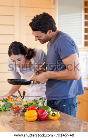 Portrait of a young couple cooking with a pan in their kitchen
