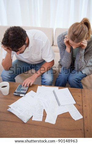 Portrait of a young couple doing their accounting in their living room