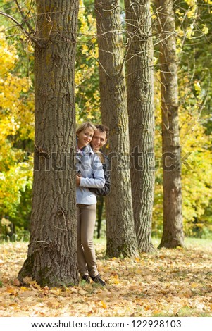 Portrait of a young couple hiding beyond the trees