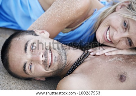 Portrait of a young couple in love laying down on a white sand beach, smiling at camera.
