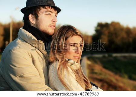 Portrait of a young couple in  warm clothes watching sunset.