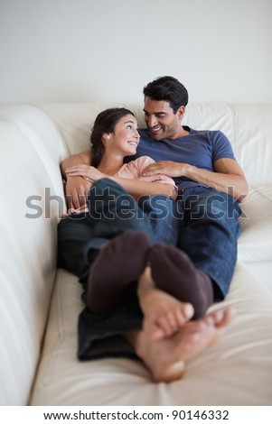 Portrait of a young couple lying on a sofa while looking at each other