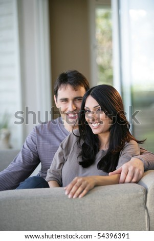 Portrait of a young couple smiling on a sofa