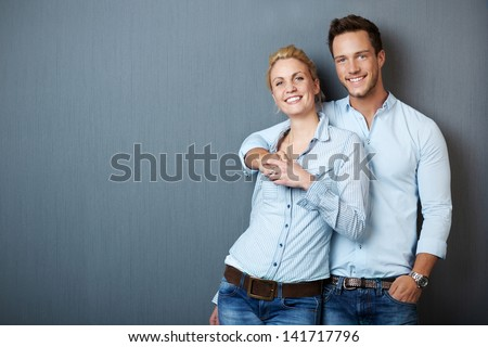 Portrait of a young couple standing against blue gray background