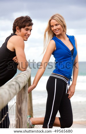 Portrait of a young couple standing at a wooden fence by the ocean. The man is leaning on the fence, and both are smiling. Vertical shot.