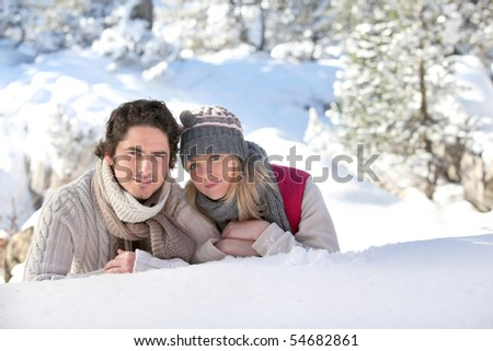 Portrait of a young couple stretched out on the snow - stock photo