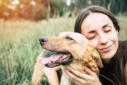 Portrait of a young cute woman with her beautiful dog lying outdoors in park. Shelter dog and volunteer concepts.