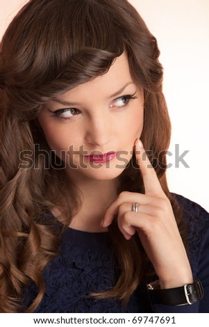 Portrait of a young cute woman with her finger on cheek