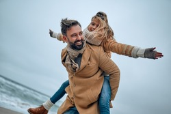 Portrait of a young dad and his cute daughter who have fun on the beach in winter.