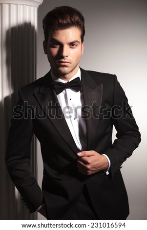 Portrait of a young elegant business man fixing his jacket while looking at the camera.
