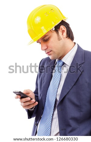 Portrait of a young engineer looking at his cellphone against white background
