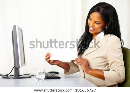 Portrait of a young executive female at work while show a white card