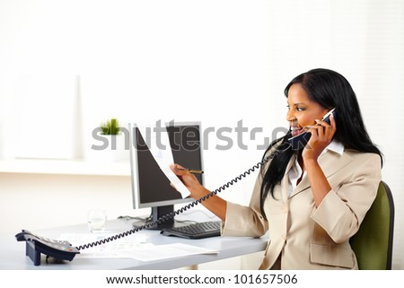 Portrait of a young executive on phone while looking to documents