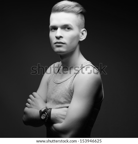 Portrait of a young fashionable man in trendy shirt posing over grey background with hands crossed. Perfect skin and haircut. Vintage dress watch on a hand. Hipster style. Studio shot