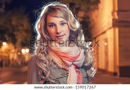 Portrait of a young female businesswoman in night city. Close-up, shallow DOF. Headshot of 25 year old female in night megapolis. Copy space. Backlit image. Vintage Color.