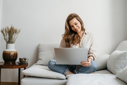 Portrait of a young female freelancer sitting on the couch and using laptop at home happily. High quality photo
