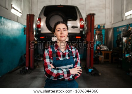 Portrait of a young female mechanic in uniform, posing with her arms crossed. In the background there is an auto repair shop and a car on a lift. Photo stock ©