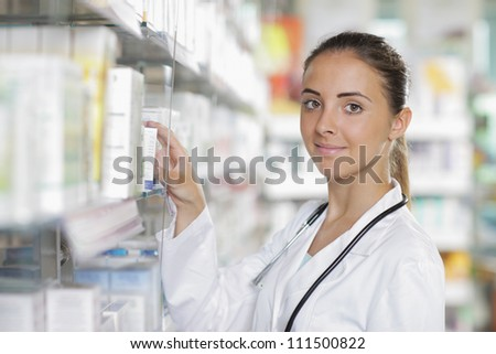 Portrait of a young female pharmacist selecting a medication