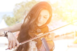 Portrait of a young female playing the violin. With sunshine. Color toned image.
