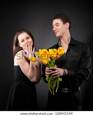 Portrait of a young funny couple in love with flowers over dark background