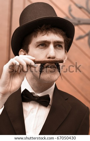 Portrait Of A Young Gentleman In A Black Suit And Top Hat Smelling Or Sniffing A Cigar While Reminiscing About The Bygone Days