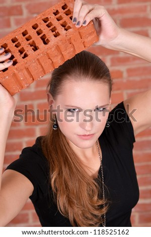 portrait of a young girl against a brick wall
