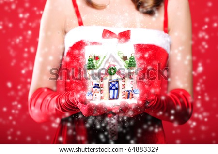 Portrait of a young girl dressed as Santa Claus on a red background. Girl gives gifts. Happy New Year and Merry Christmas!