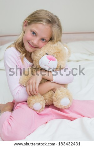 Portrait of a young girl embracing stuffed toy in bed at home