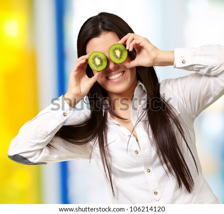 portrait of a young girl holding kiwi slices in front of her eyes indoor
