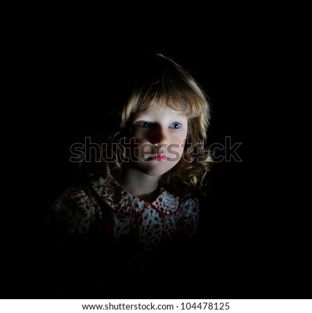 Portrait of a young girl in a dark room on a black background